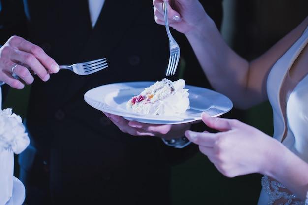 Braut und bräutigam probieren luxus hochzeitstorte mit rosen verziert