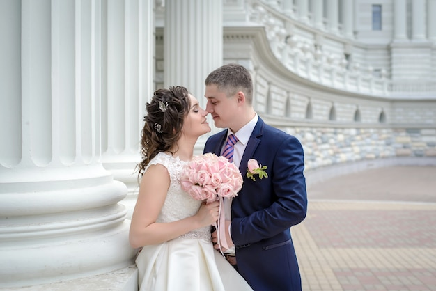Braut und bräutigam schauen sich in der nähe der weißen säulen an