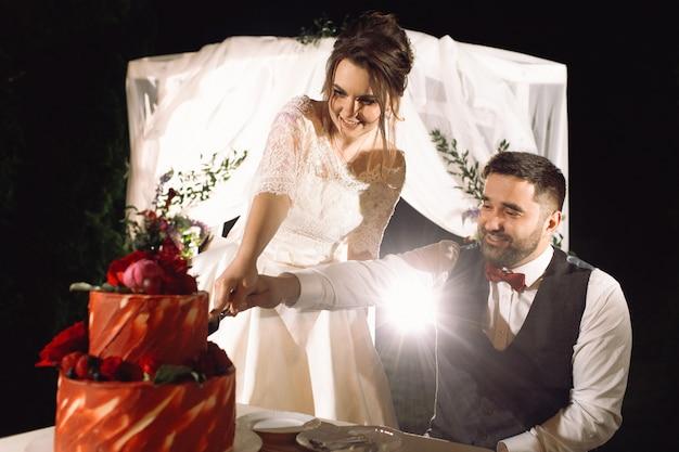Braut und bräutigam schmecken den roten hochzeitskuchen, der vor dem altar in der nacht steht
