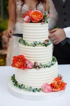 Braut und bräutigam schneiden die hochzeitstorte dekorierte blumen. festliche weiße schöne hochzeitstorte. paar mit einem messer in den händen schneidet einen kuchen in der party im restaurant. hochzeitspaar schneiden ihren kuchen