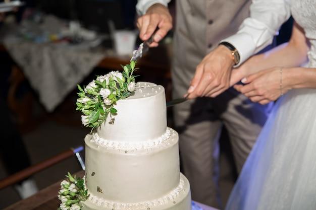 Braut und bräutigam schneiden die hochzeitstorte. der kuchen ist mit beigen und grünen rosen dekoriert.