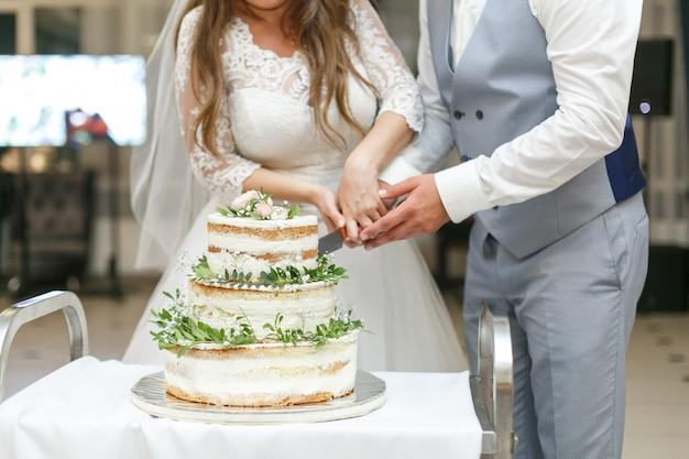 Braut und bräutigam schneiden die hochzeitstorte.