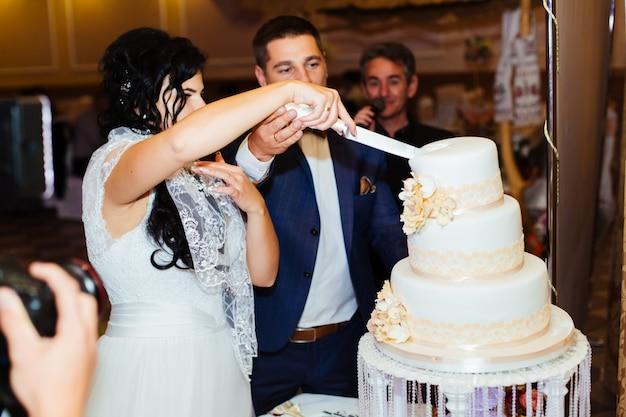 Braut und bräutigam schneiden die hochzeitstorte