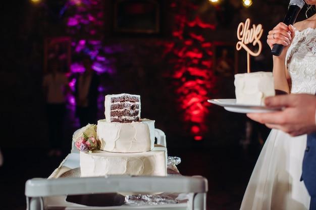 Braut und bräutigam schneiden ihre hochzeitstorte. schöner kuchen mit einer geschnittenen und sichtbaren füllung. hochzeitstorte mit dem wort liebe, dem konzept der hochzeit.