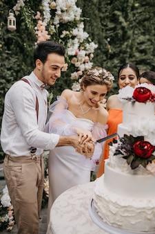 Braut und bräutigam schneiden kuchen zusammen, während die gäste sie im freien beobachten