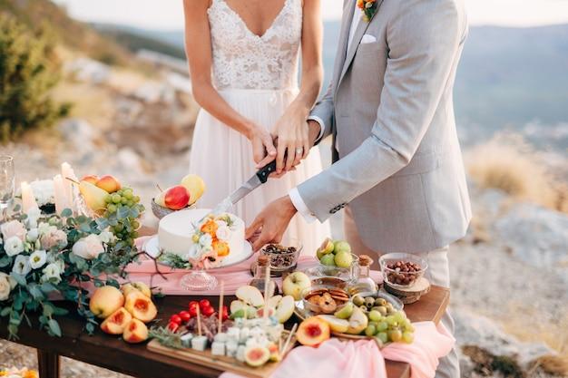 Braut und bräutigam schneiden nach der hochzeitszeremonie auf dem berg während eines buffettisches einen kuchen