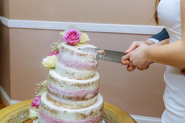 Braut und bräutigam schneiden zusammen die hochzeitstorte.