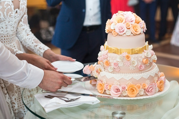 Braut und bräutigam schnitten den köstlichen hochzeitskuchen, der mit beige verziert wurde