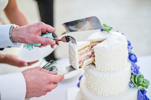 Braut und bräutigam schnitten die weiße hochzeitstorte, die mit blauen blumen verziert wurde