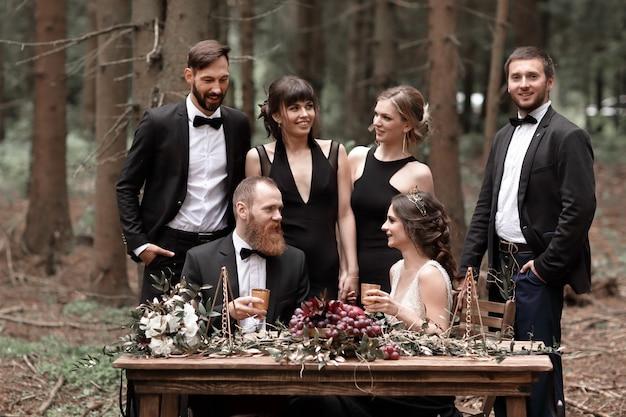 Braut und bräutigam sitzen am gedeckten tisch für eine feier im wald
