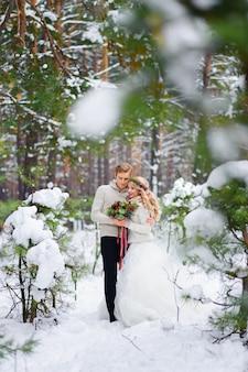 Braut und bräutigam sitzen auf dem baumstamm im winterwald. nahansicht. winterhochzeitszeremonie.
