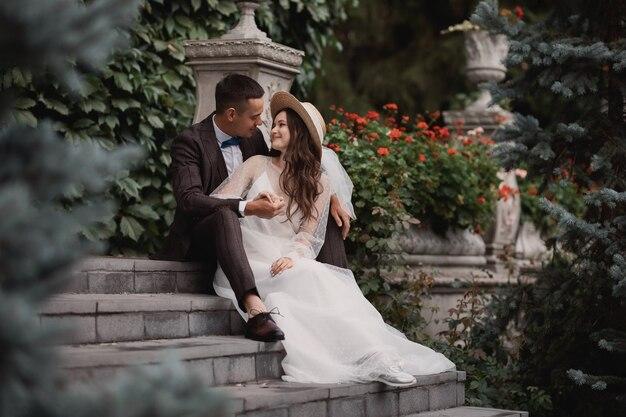 Braut und bräutigam sitzen auf den stufen im vintage-garten