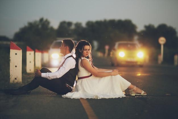 Braut und bräutigam sitzen mit dem rücken zueinander auf der straße in den strahlen der scheinwerfer vorbeifahrender autos