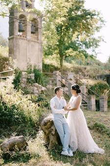 Braut und bräutigam sitzen umarmend in der nähe des alten glockenturms in der nähe der kirche in prcanj