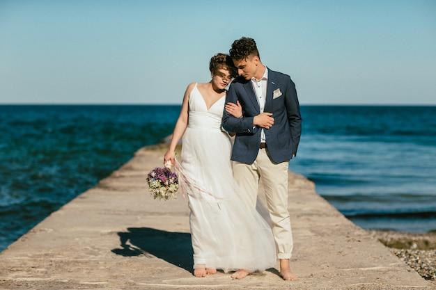 Braut und bräutigam stehen auf dem pier