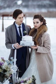 Braut und bräutigam stehen in der winternatur neben einem glastisch. sie halten eine hochzeitstorte