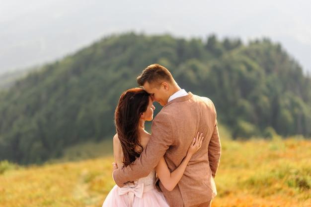 Braut und bräutigam stehen mit dem rücken und umarmen sich. sonnenuntergang. hochzeitsfoto auf einem hintergrund der herbstberge. ein starker wind bläst haare und kleid auf.