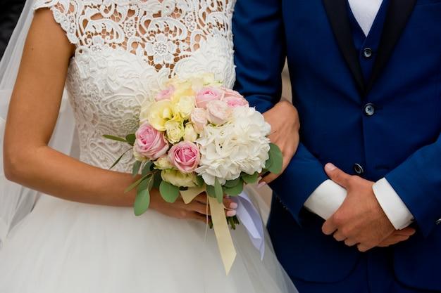Braut und bräutigam stehen mit den händen zusammen.