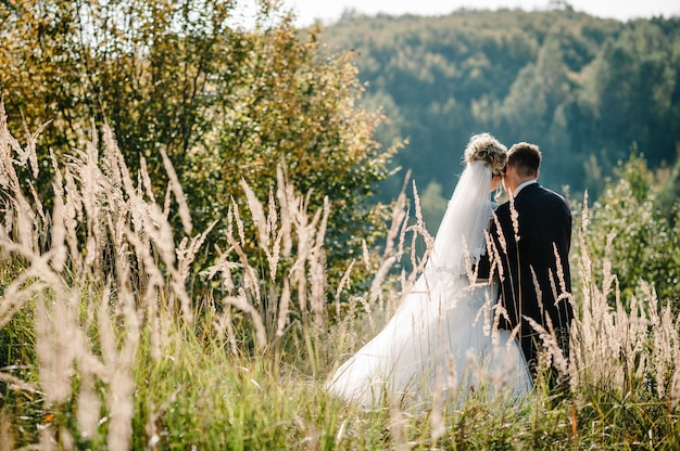 Braut und bräutigam stehen nach der hochzeitszeremonie auf dem feld.