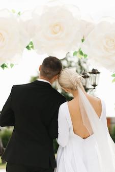 Braut und bräutigam treten vor dem hintergrund des hochzeitsbogens zurück