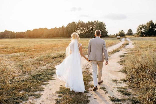 Braut und bräutigam umarmen sich am hochzeitstag und gehen bei sonnenuntergang die straße entlang zum wald