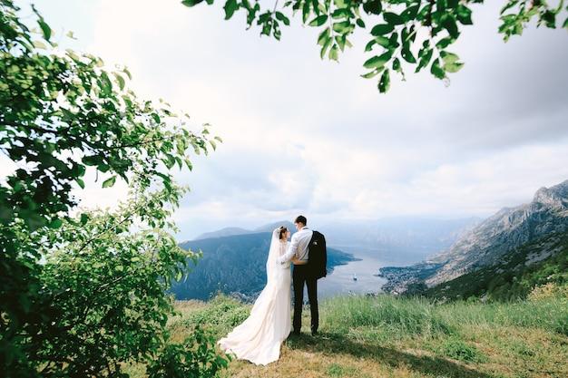 Braut und bräutigam umarmen sich auf dem berg lovcen vor dem hintergrund des panoramas der bucht von kotor