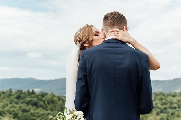 Braut und bräutigam umarmen sich bei der hochzeit in der natur