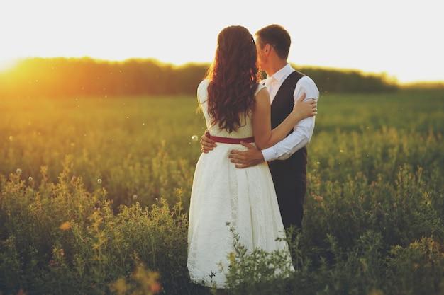 Braut und bräutigam umarmen sich im park im sonnenuntergangslicht