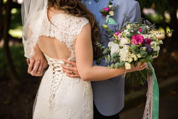 Braut und bräutigam umarmen sich im park. spitze auf der rückseite des brautkleides. hochzeitsstrauß in der hand der braut.