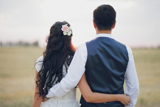 Braut und bräutigam umarmen sich und begegnen dem sonnenuntergang. hochzeit