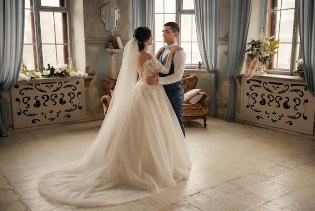 Braut und bräutigam umarmen sich und stehen vor dem fenster. liebe, hochzeitskonzept. schöne hochzeit, ehemann und ehefrau, liebhaber mann frau, braut und bräutigam.