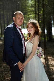 Braut und bräutigam umarmen und küssen sich im dunklen wald in der sonne. hochzeit in der natur, porträt eines verliebten paares im park