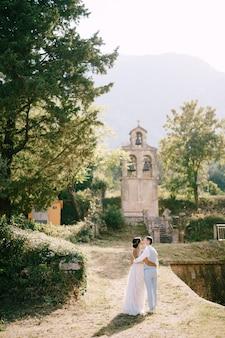 Braut und bräutigam umarmen und küssen sich in der nähe des alten glockenturms in der nähe der kirche in prcanj-rückansicht