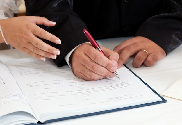 Braut und bräutigam unterzeichnen heiratsurkunde
