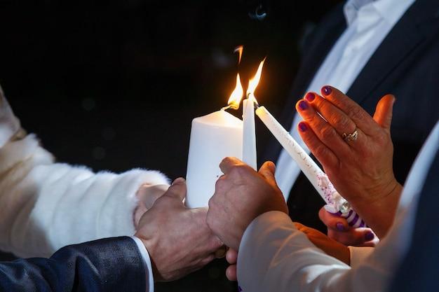 Braut und bräutigam zünden an einem hochzeitstag gemeinsam eine kerze an