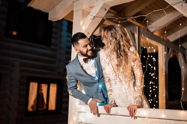 Braut und bräutigam zusammen mit dekor küssen, umarmungen in luxusdekoration am hochzeitstag