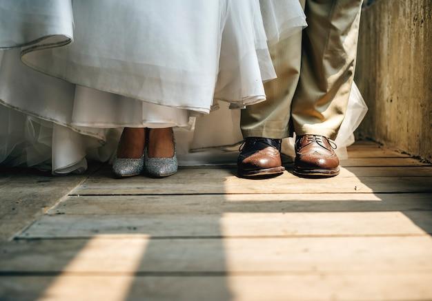 Braut- und bräutigamfüße stehen auf holzboden