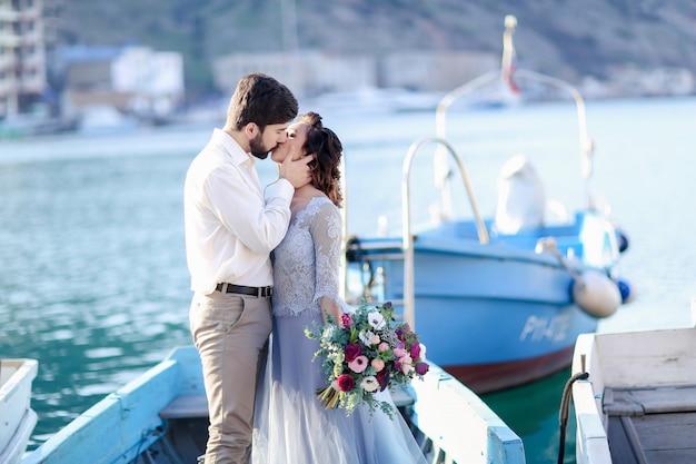 Braut- und bräutigamhochzeit auf pier mit booten auf dem meer