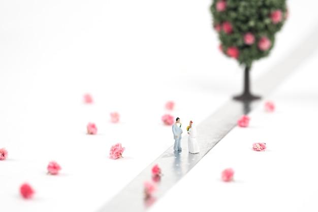 Braut- und bräutigamminiaturpaare auf silbernem band