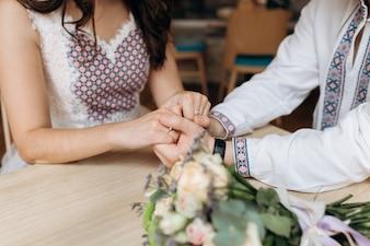 Braut und Bräutigam in ethnischer Kleidung halten sich die Hände sitzen
