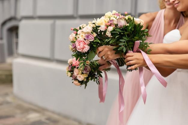 Braut und brautjungfer halten hochzeitssträuße