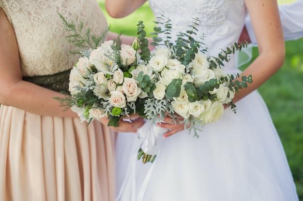 Braut und brautjungfer mit blumensträußen auf hochzeitsweg im park