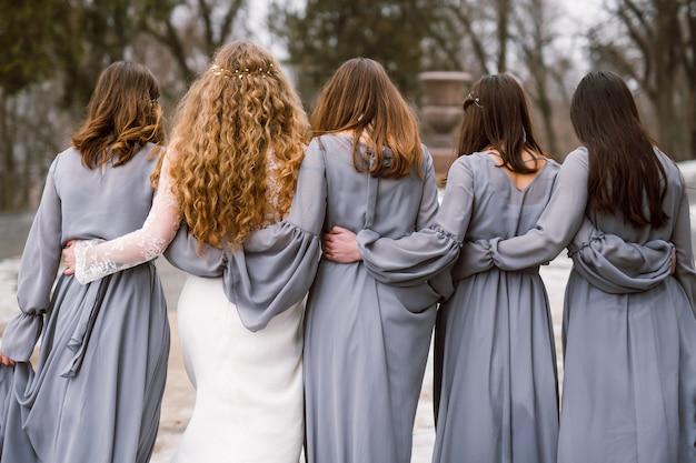 Braut und brautjungfern gehen weg und tragen die gleichen kleider