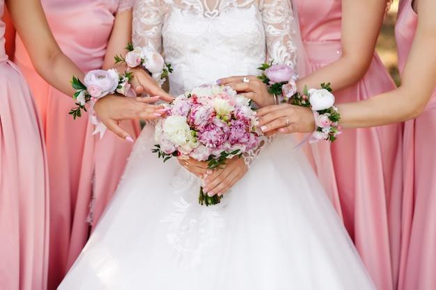 Braut und brautjungfern halten hochzeitsstrauß