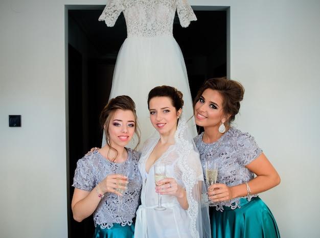 Braut und brautjungfern in blauen kleidern trinken champagner vor einem brautkleid