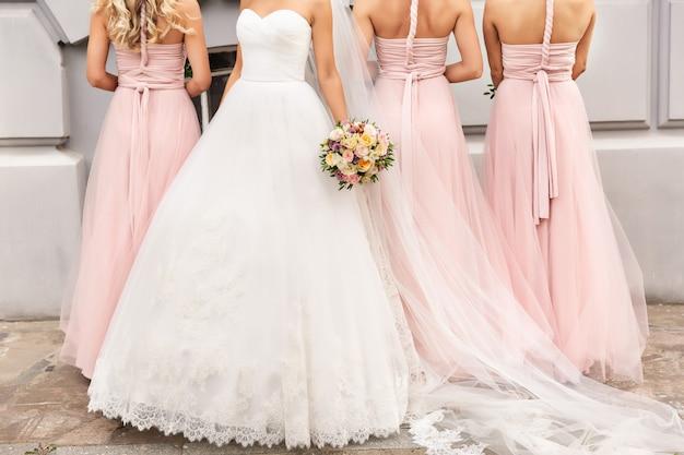 Braut und brautjungfern in rosa kleidern, die mit blumensträußen am hochzeitstag aufwerfen