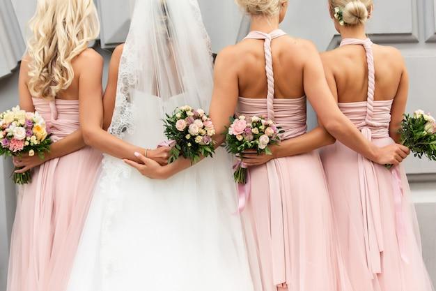 Braut und brautjungfern in rosa kleidern umarmen sich und posieren mit blumensträußen am hochzeitstag