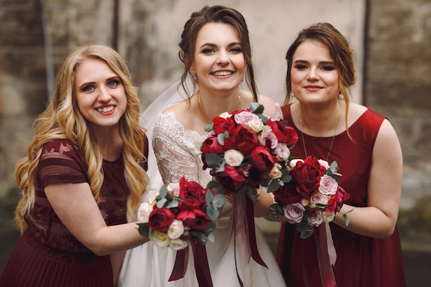 Braut und brautjungfern in roten kleidern posieren draußen auf der alten nassen straße