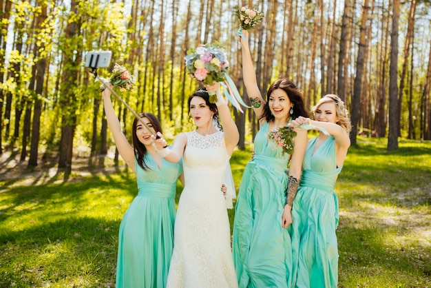 Braut und brautjungfern mit hochzeitssträuße. sonniger hochzeitsempfang freudiger moment.