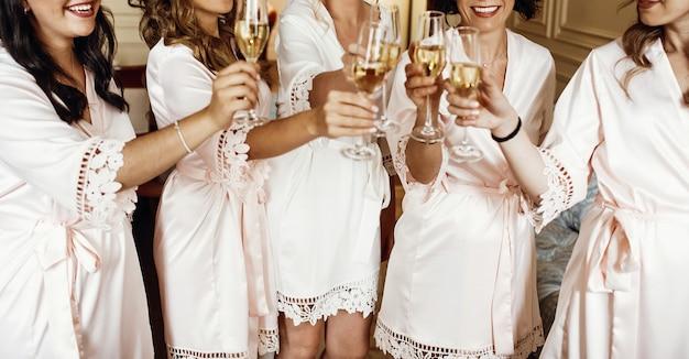 Braut und brautjungfern stehen in seidengewändern mit champagnergläsern